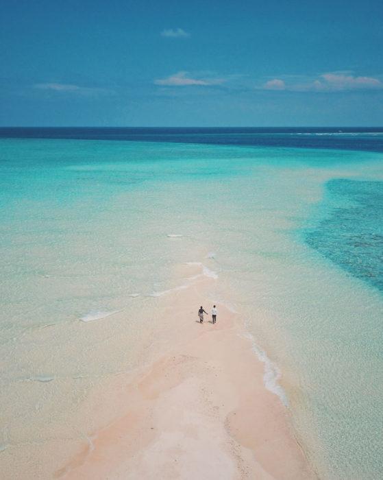 Pareja de novios caminando en medio de una playa que conecta al mar