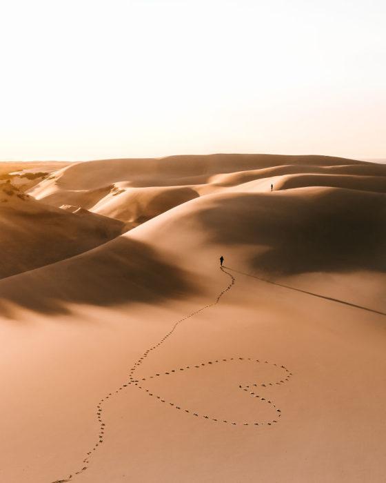 Persona caminando por el desierto y formando un corazón con sus pasos