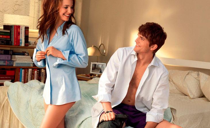 una mujer se abrocha la camisa a un lado de la cama donde está sentado un hombre con la camisa abierta