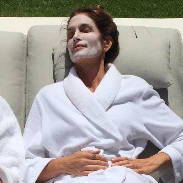 una mujer recostada con una bata blanca y una mascarilla en su cara