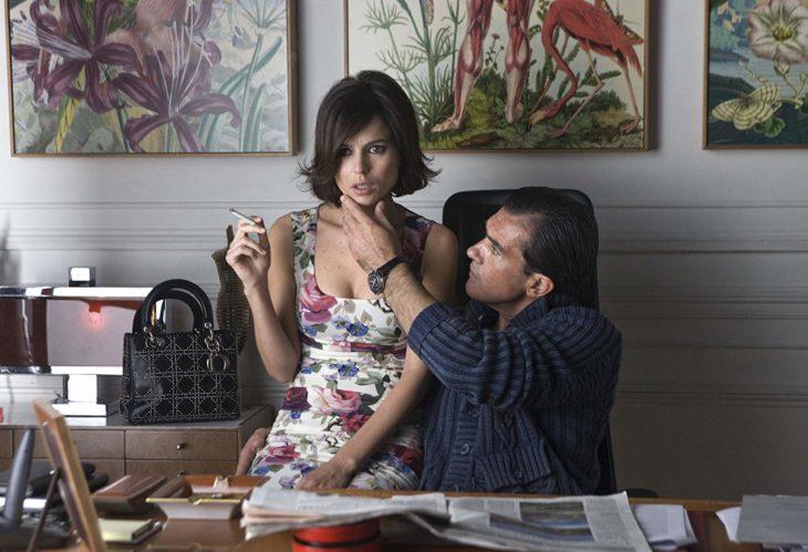 un hombre ve el rostro de una mujer que fuma sentada a su lado