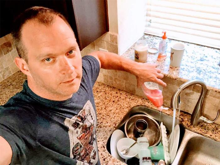 Hombre tomándose una selfie mientras está a punto de lavar los platos en su cocina
