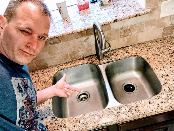 Hombre mostrando lo limpio que se encuentra su lavatrastes luego de limpiarlo