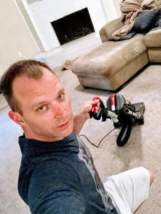Hombre tomandose una selfie mientras toma la aspiradora y empieza a limpiar su alfombra