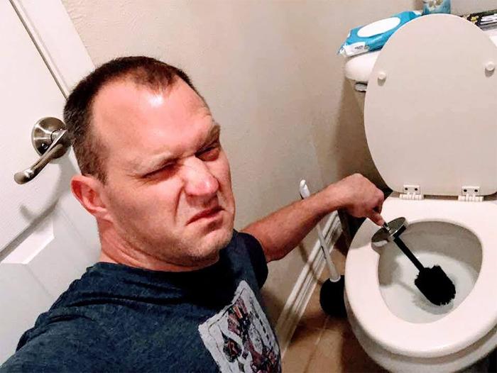 Hombre tomandose una foto mientras está lavando el inodoro con un cepillo