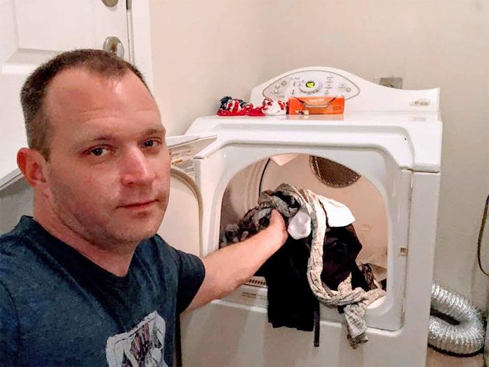 Hombre metiendo ropa limpia a la secadora