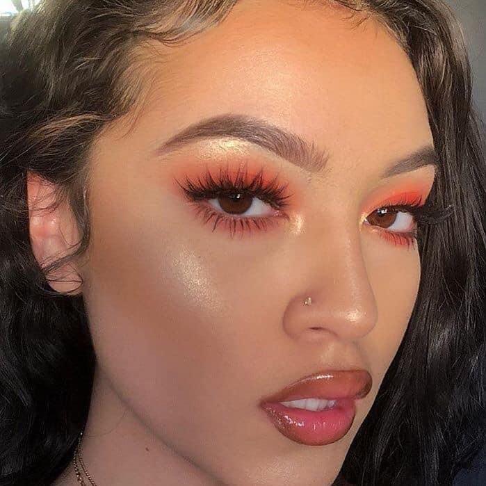 Chica usando un maquillaje monocromático en colores naranja