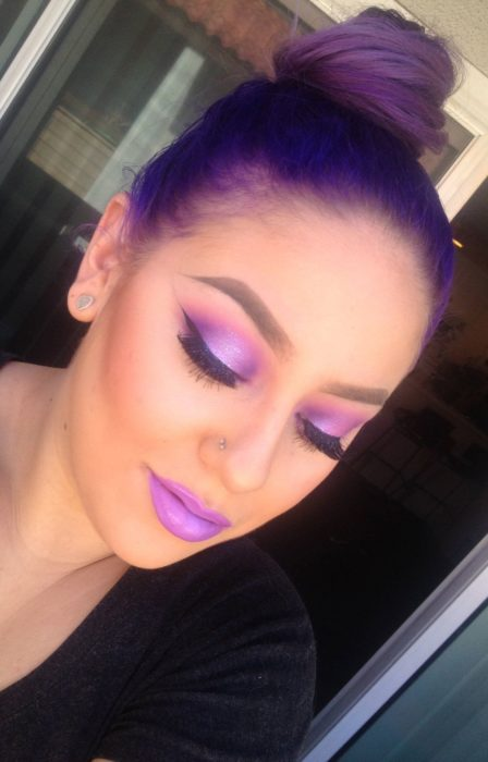 Chica usando un maquillaje monocromático de color morado en ojos y labios
