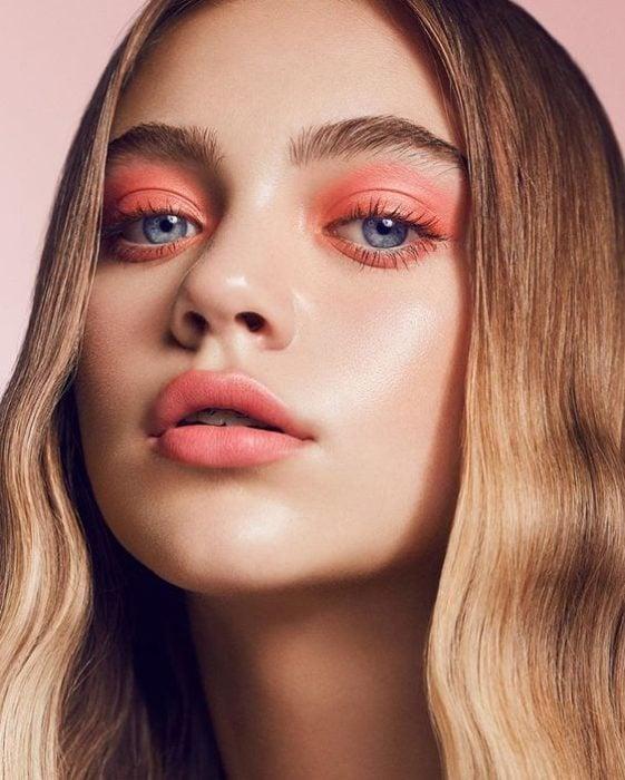 Chica usando un maquillaje monocromático en colores pasteles en ojos y labios