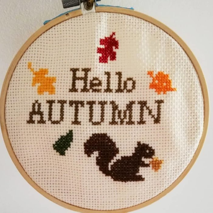 un bastidor y lienzo para bordar punto de cruz con un diseño que dice 'Hello autumn'