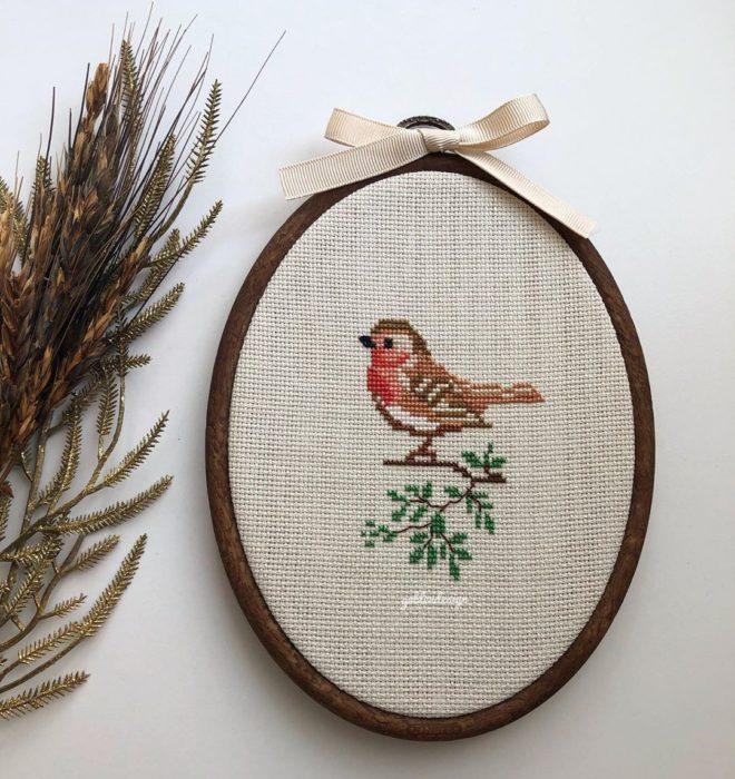 un ovalo con un pájaro sobre una rama bordado en punto de cruz