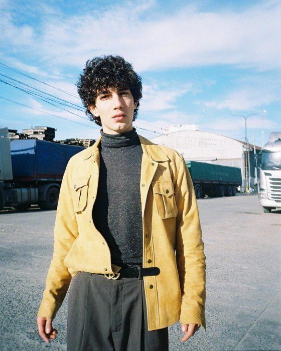 Jorge López Astorga, actor de serie de Netflix que interpreta a Valerio; joven de cabello chino y negro con saco de gamuza amarillo y camisa gris con cuello de tortuga