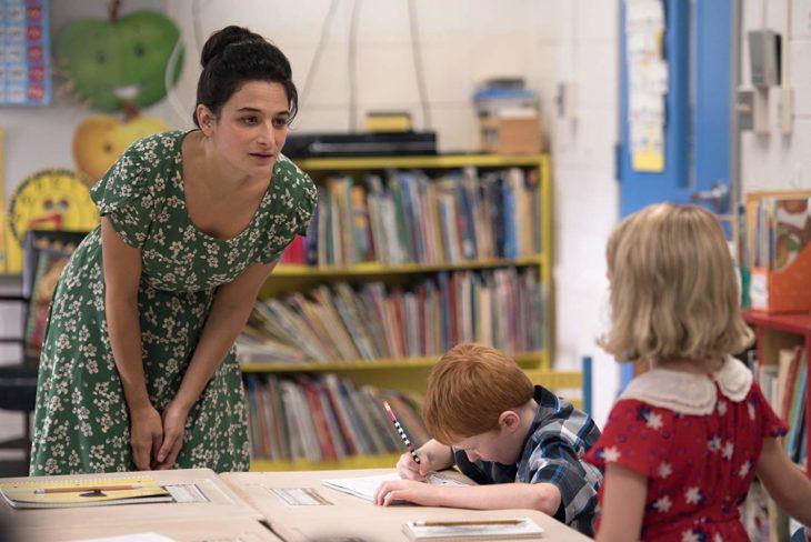 Una maestra inclinada le habla a una niña rubia de espaldas con vestido rojo con lunares blancos