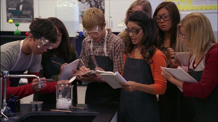 un grupo de estudiantes en un laboratorio con mandiles y lentes de protección