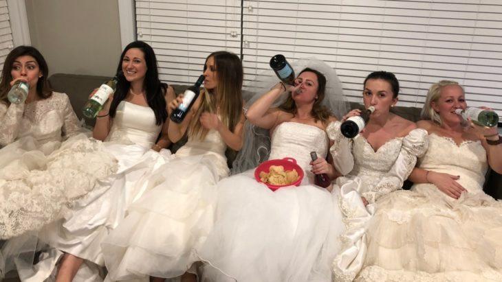 seis mujeres sentadas en un sofá vestidas de novia y tomando de botellas de vino
