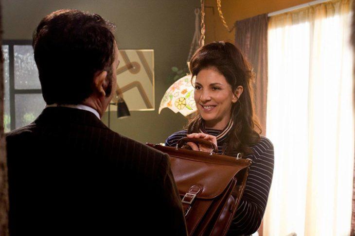 Una mujer sonriente le entrega a un hombre un portafolio