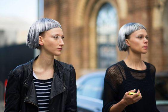 dos mujeres con corte 'bowl' en cabello platinado caminan por una calle con fondo de un edificio