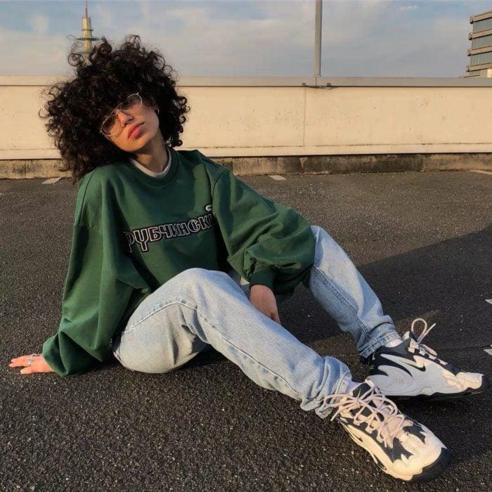 Looks tomboys; chica afroamericana con atuendo masculino, sudadera verde, mom jeans, lentes vintage de aumento y cabello chino y esponjado