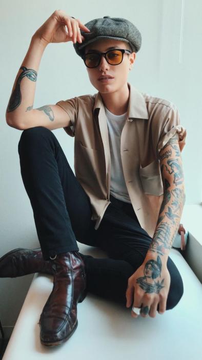 Looks tomboys; chica con atuendo masculino, con boina bohemia, pantalón de mezclilla negro, camisa café y botas, con tatuajes en los brazos