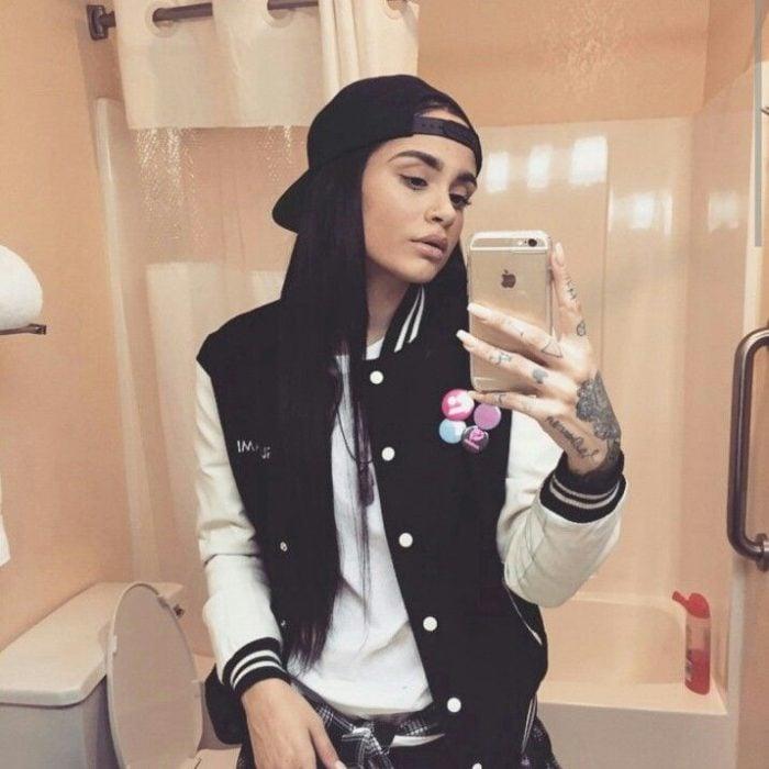 Looks tomboys; chica con atuendo masculino, jersey deportivo negro, con cachucha, tomándose una foto frente al espejo