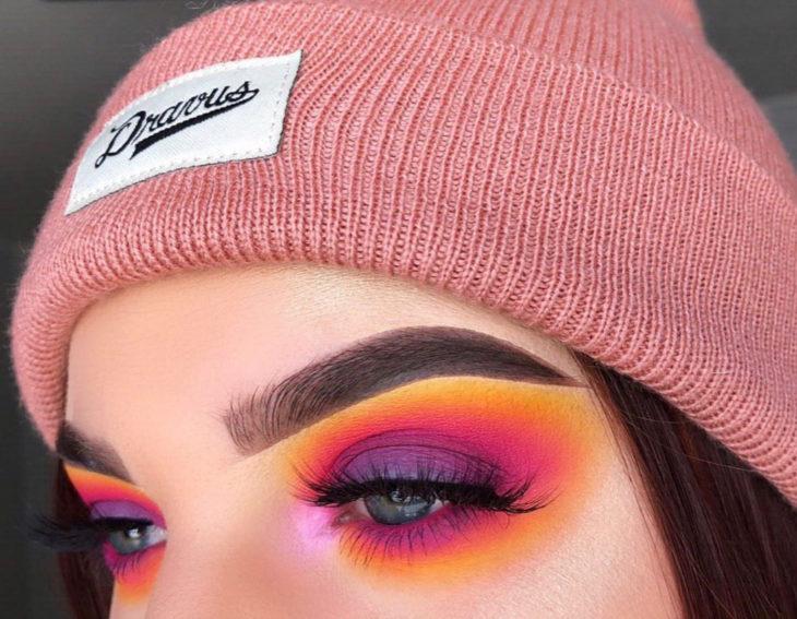 Maquillaje creativo para ojos; smokey eyes con sombras amarillas, rosas, anaranjadas y moradas