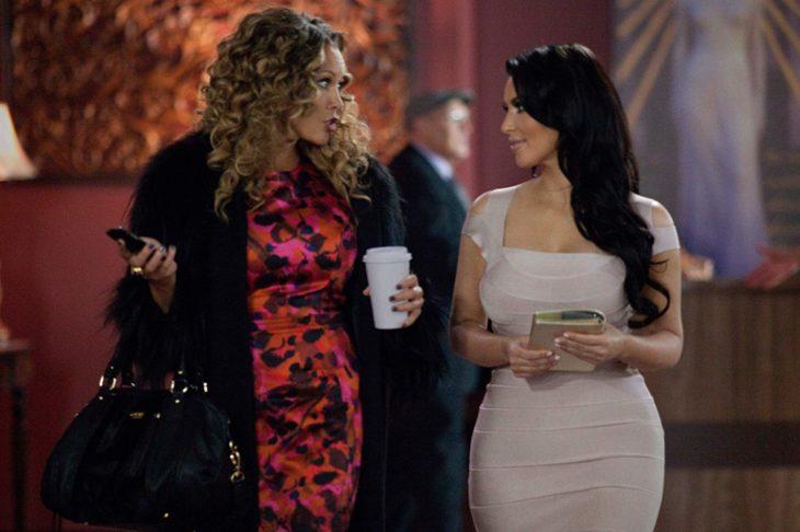 dos mujeres vestidas de coctel caminando y una lleva un vaso de café