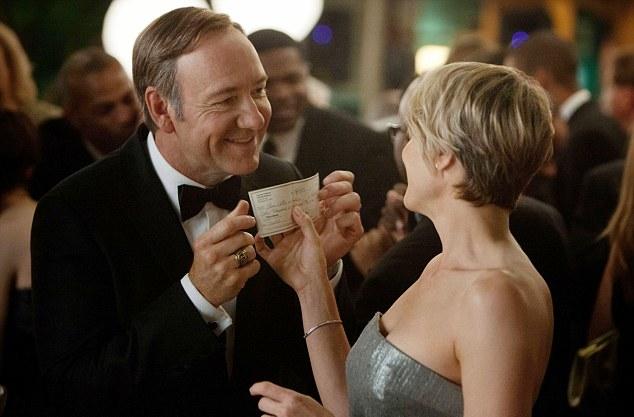 un hombre le da un cheque a una mujer, en una fiesta