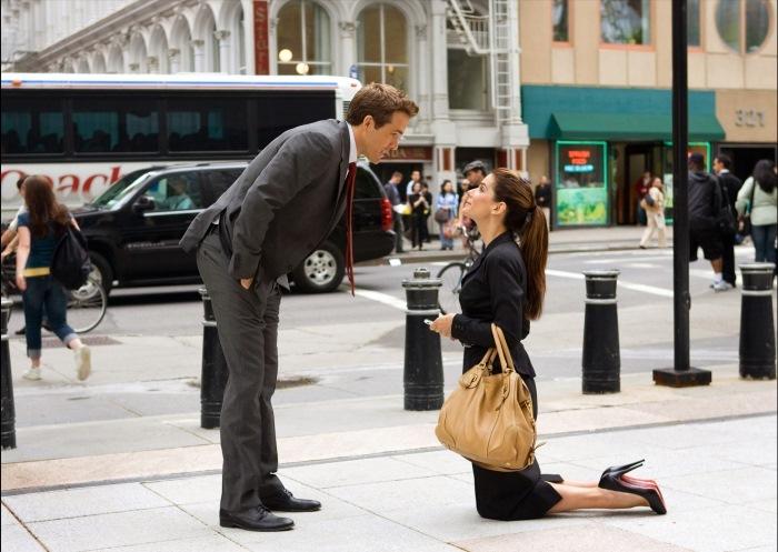 una mujer hincada ante un hombre de traje inclinado hacia ella