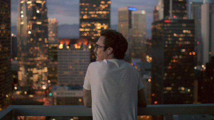 Joaquin Pohenix en un balcón viendo la ciudad en la película Her