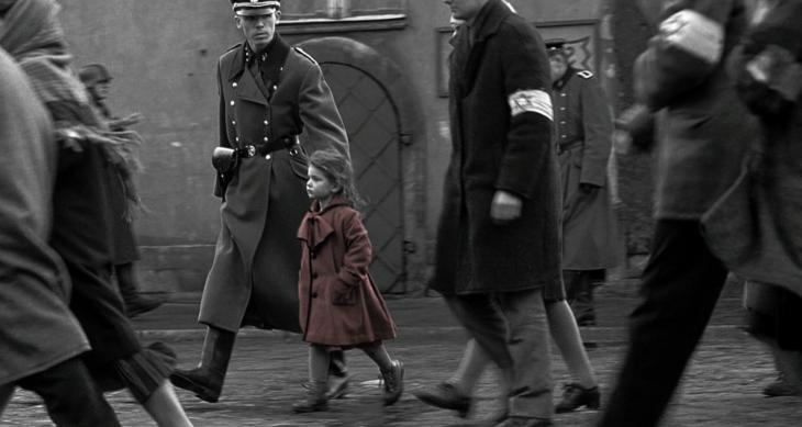 Escena de la película Schneider, niña con saco rojo caminando por las calles