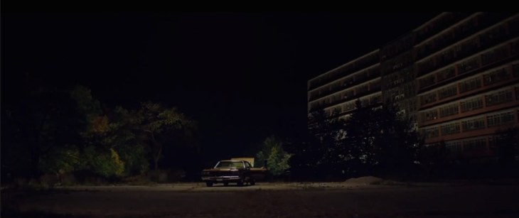 Escena de la película It Follows, carro estacionado fuera del edificio