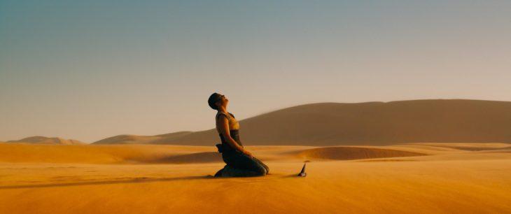 Escena de la película Mad Max: Fyru Road, Charlize Theron incada en la arena