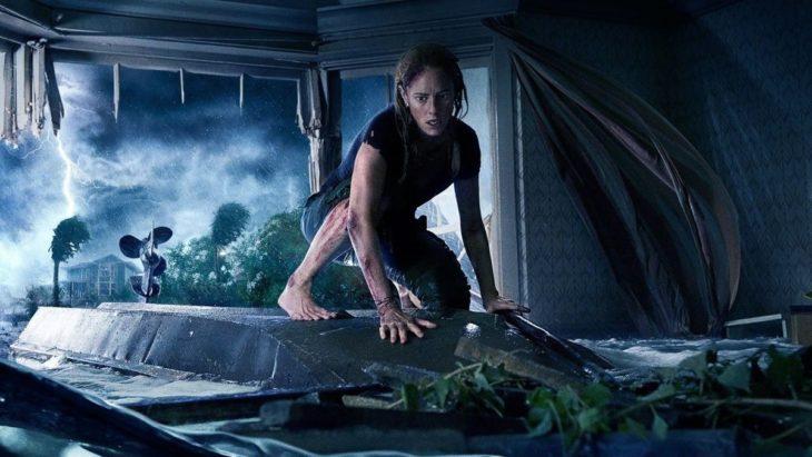 Mujer arriba de un carro escondida de un cocodrilo gigante, escena de la película Crawl