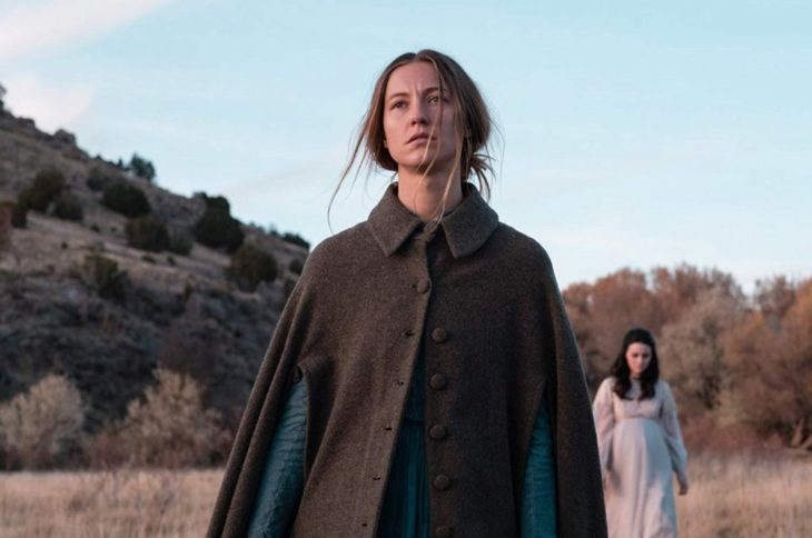 Escena de la película The Wind, mujer con capa de botones caminando a través desierto