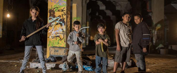 Escena de la película Vuelven, grupo de niños bajos los puentes, listos para vencer sus miedos