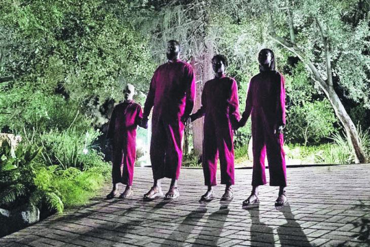 Escena de la película Nosotros, familia tomada de las manos llevando jumpers en tono rojo