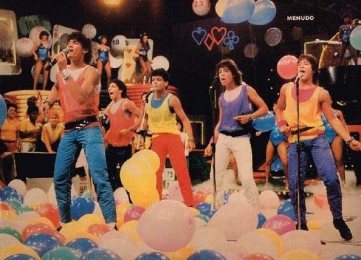 Hombres con pantalones de colores cantando y bailando, escena de la película Menudo, agrupación Menudo