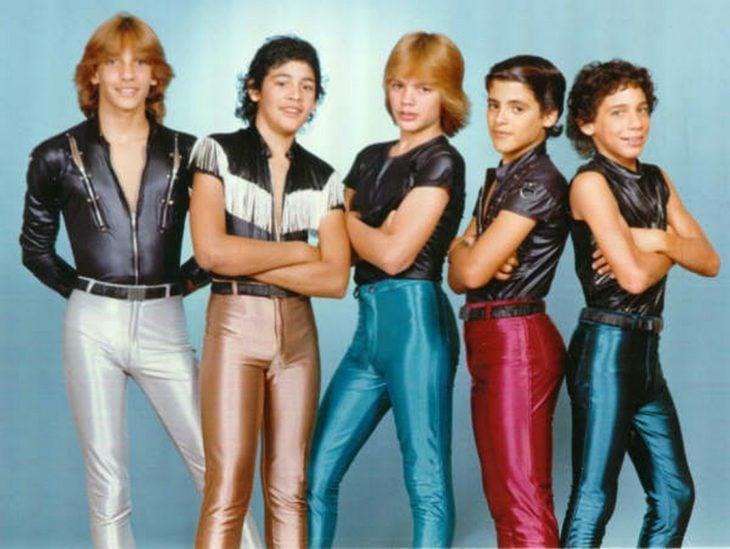 Hombres con leotardos en colores metálicos, integrantes de Menudo