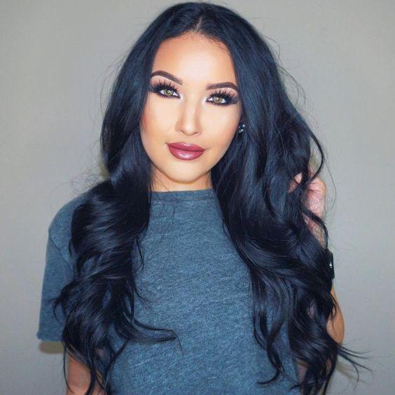 una mujer con cabello muy largo negro con reflejos ligeros azules, con camiseta gris oscura