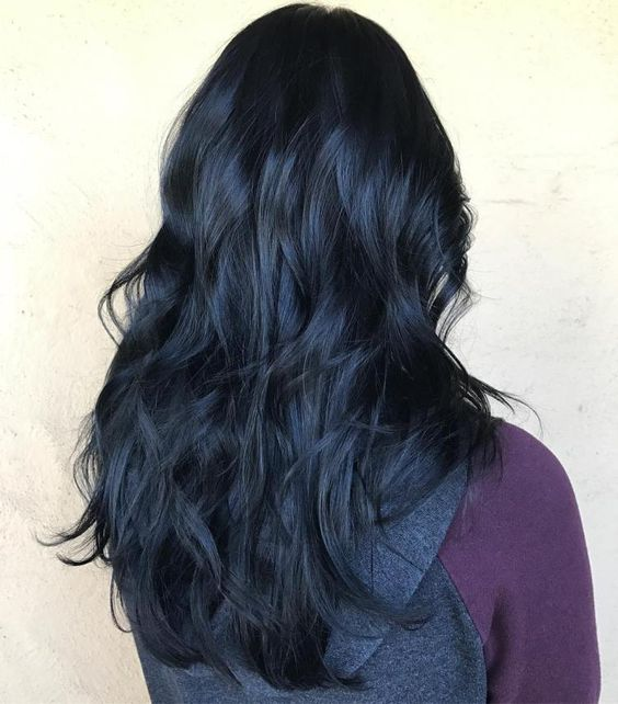 un cabello largo ondulado oscuro con reflejos azules
