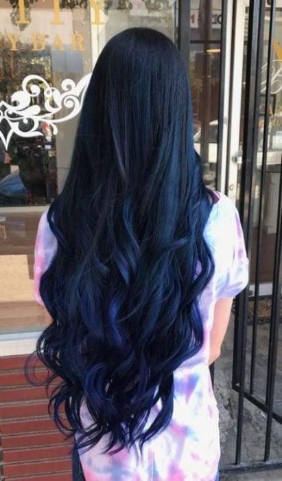 una mujer de espaldas con vestido de colores ycabello que llega hasta las caderas negro con reflejo azul