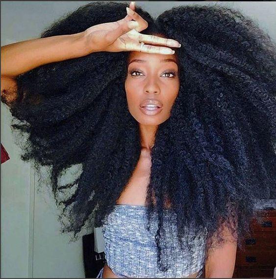 una mujer con cabello chino afro negro con reflejos azulados se toca la frente con dos dedos