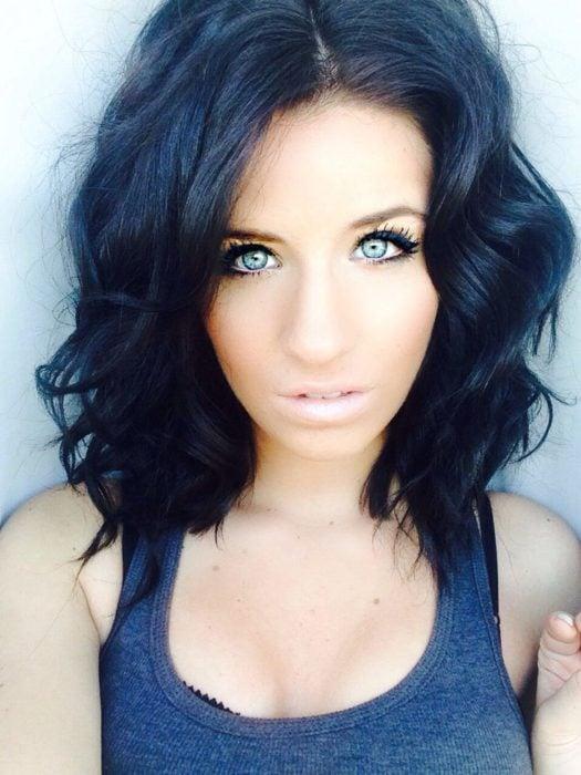 una mujer con cabello a los hombros ondulado oscuro con reflejos azulados