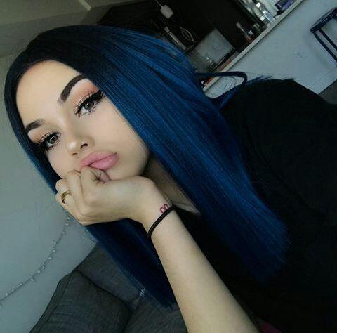 una mujer con pelo lacio negro azulado recarga su barbilla sobre su brazo derecho