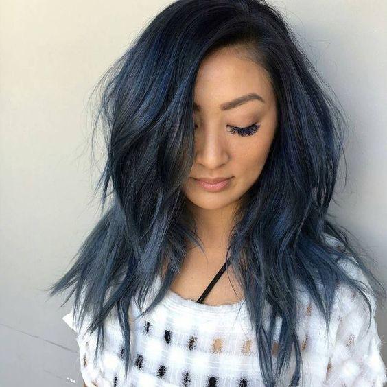 mujer vestida con blusa blanca de cuadros, cabello lacio alborotado con leves reflejos azulados