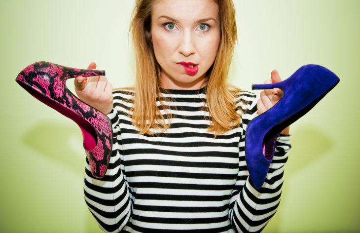 Mujer con dos zapatillas diferentes en la mano y con gesto indeciso