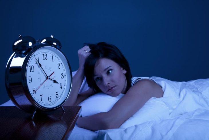 Mujer que no puede dormir viendo el reloj