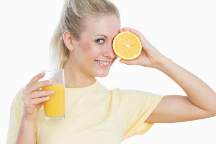 Mujer tapando su ojo con la mitad de una naranja