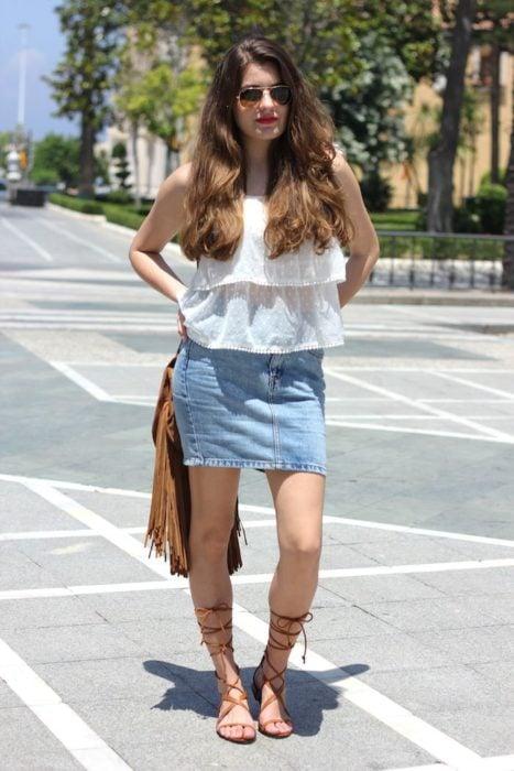 Mujer vestida con blusa blanca, falda de mezclilla y sandalias