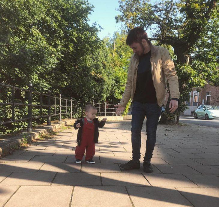 Rob Molineux con su hijo Chester caminando por una banqueta en un parque